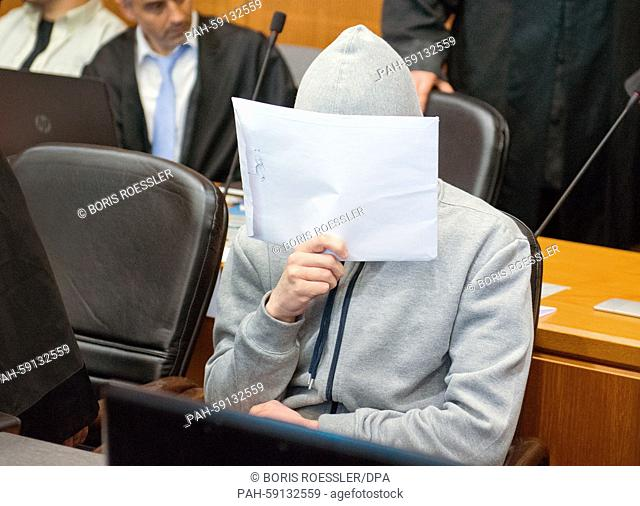 One of the defendants of the Al-Shabaab trial covers his face with an envelope at the higher regional court in Frankfurt/Main, Germany, 12 June 2015