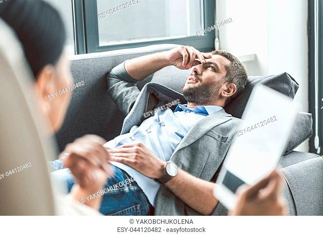 Thoughtful patient is lying on couch. Psychologist sitting afore him and holding tablet