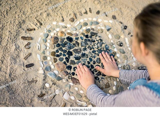 Little girl making a heart from seashells on the beach