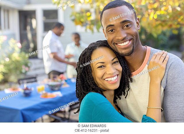 Portrait of happy couple near patio table