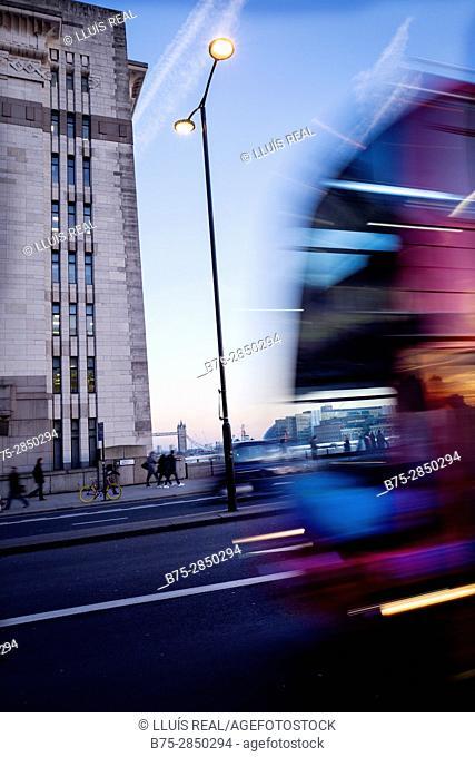 Autobus en movimiento 'London Transport'en una calle con una farola encendida y la Tower Bridge al fondo. London Bridge, Adelaide Hause, River Thames, London