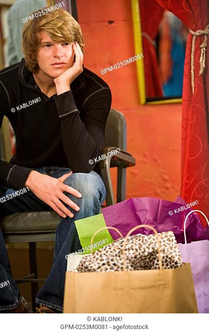 Bored young man sitting by shopping bag