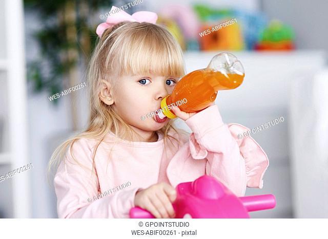 Portrait of blond little girl drinking juice