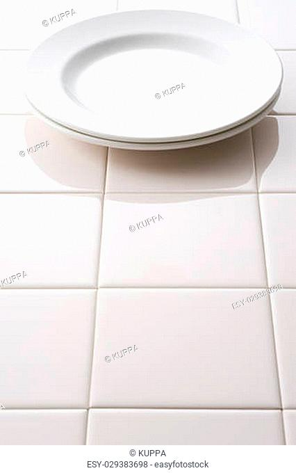 Empty white plate on tile floor background