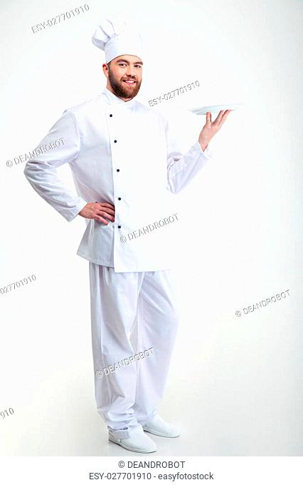 Portrait of a happy male chef cook standing with plate isolated on a white backgorund