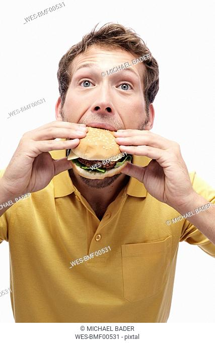 Young man eating Hamburger, portrait, close-up