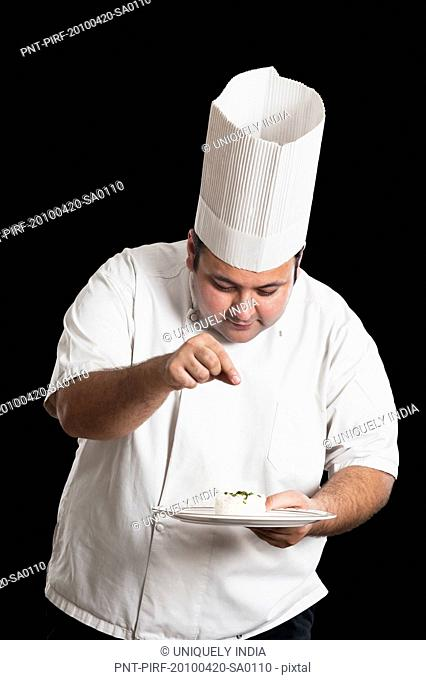 Chef sprinkling cumin seeds on a plate of rice