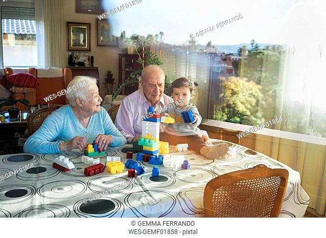 Great-grandparents and baby girl playing together with plastic building bricks at home