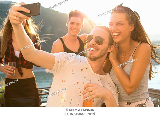 Young man taking selfie with female friend at waterfront roof terrace party, Budapest, Hungary