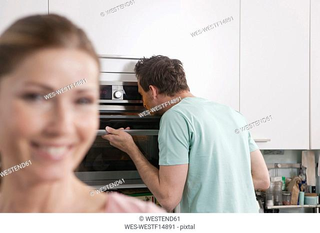 Germany, Man looking into oven with woman smiling in foreground