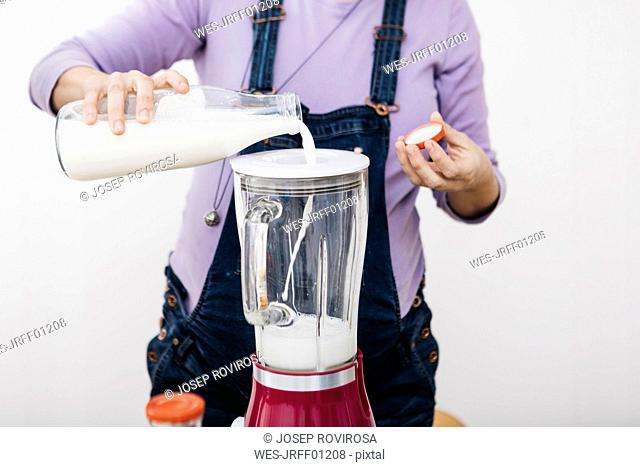Pregnant woman pouring milk into a blender for preparing smoothie, partial view