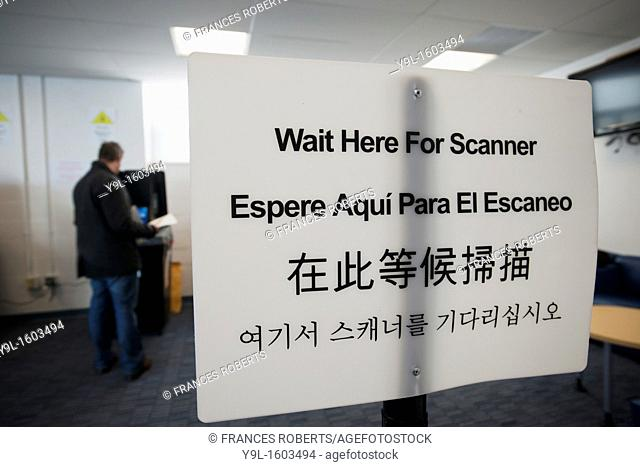 A sign instructs voters, in English Spanish, Chinese and Korean, to wait for the scanner, to cast their ballots in New York in Washington Heights on election...