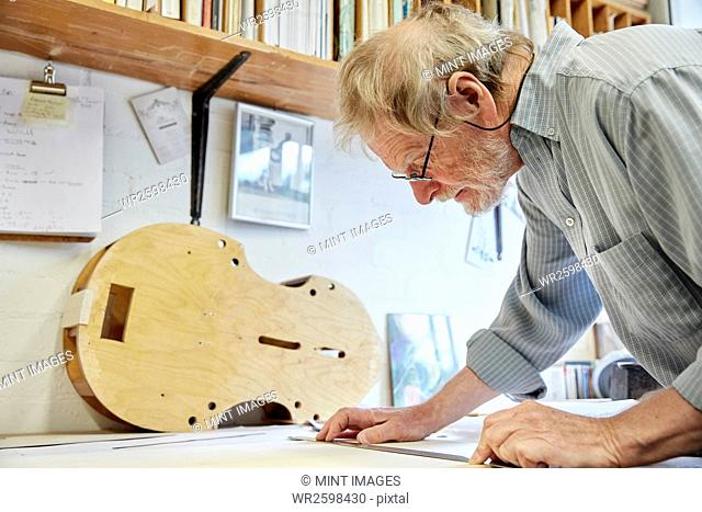 A violin maker at his drawing board drawing out the plans and outline for a new instrument