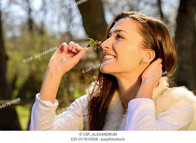 Young woman smelling wild flower