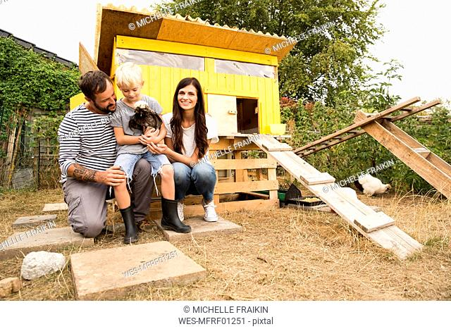 Portrait of happy family with Polish chicken at chickenhouse in garden