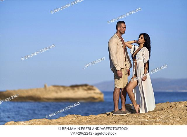 young couple at Mediterranean beach. Greek ethnicity. In holiday destination Hersonissos, Crete, Greece