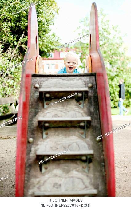 Smiling boy climbing up slide