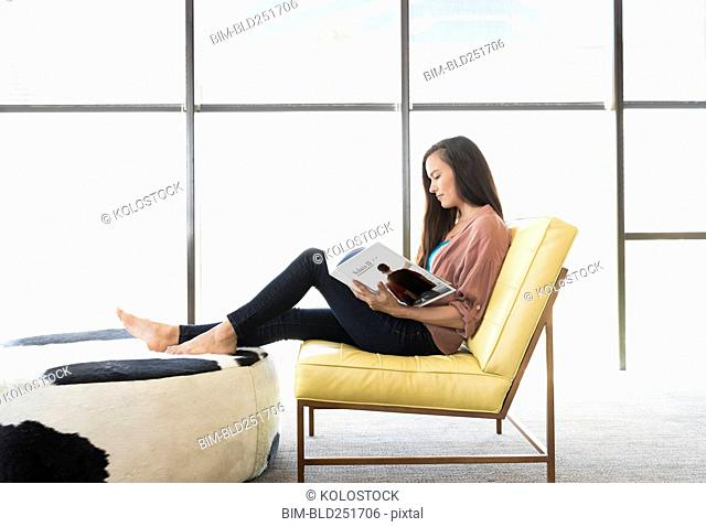Mixed race woman sitting on chair reading book