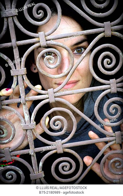 Young woman looking through a fence of a window in the Medina of Fez, Morocco, Africa