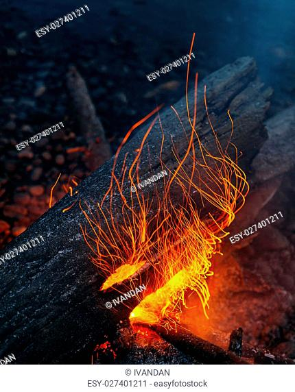 Magic fire on the river bank . Sparks, flames and other wonderful backgrounds for your text