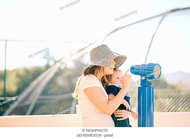 Mother and son at playground, looking through telescope