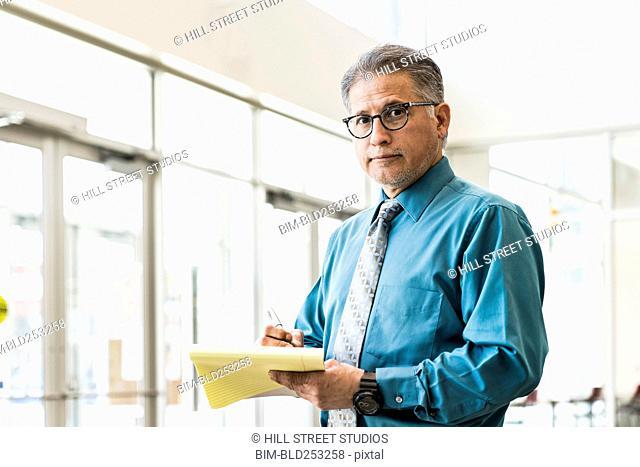 Hispanic businessman writing on notepad
