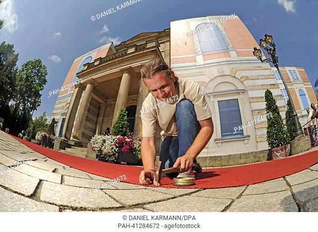 Workers roll out the red carpet for the opening of the Bayreuth Festival 2013 in Bayreuth, Germany, 25 July 2013. The one-month Wagner festival is Germany's...