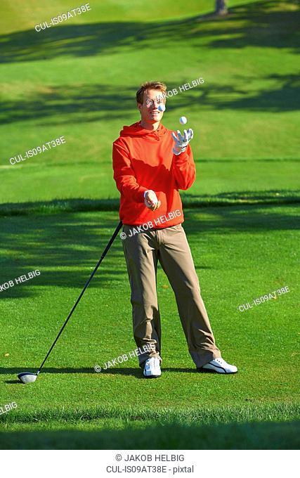Full length front view of golfer juggling golf balls smiling