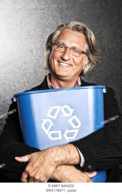 Studio portrait of Caucasian man actor holding a blue recycling bin to his chest