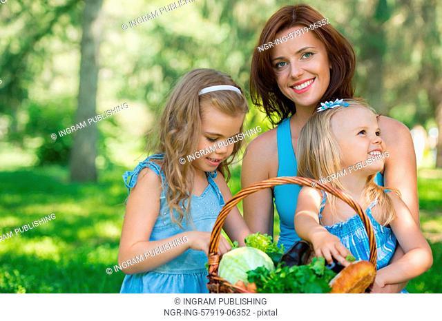 Mother with two daughters in the park preparing for picnic of organic food