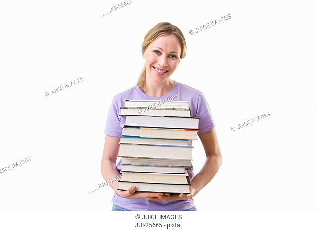 Smiling woman holding stack of text books
