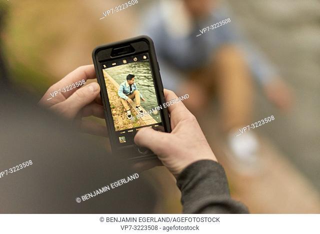 man taking photo of friend sitting at river, with smartphone, at river Eisbach, in Englischer Garten, in Munich, Germany