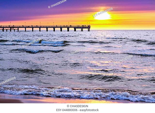 Sunset at Baltic sea in resort of Lithuania Palanga. Rays of sun shine through the low rare cirrus clouds. Pedestrian pier extends into the sea