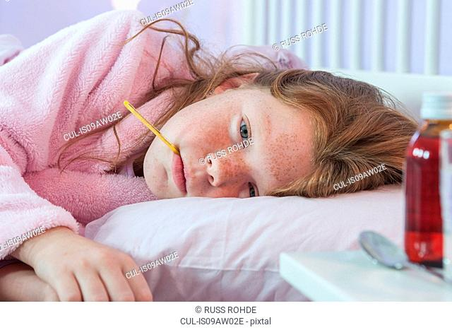 Close up of girl lying in bed with thermometer in her mouth