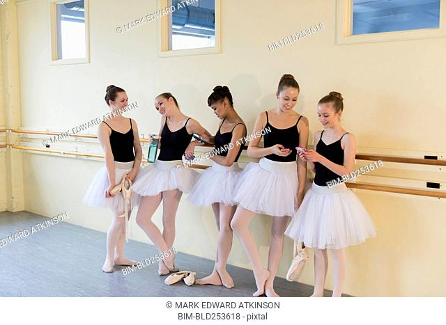 Girls talking and texting on cell phones in ballet studio