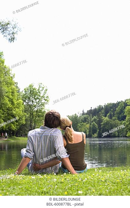 rear view of young couple sitting in park by lake