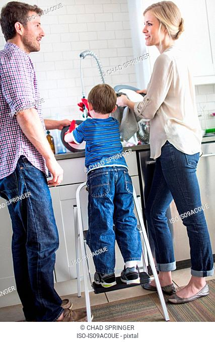 Parents and son washing dishes