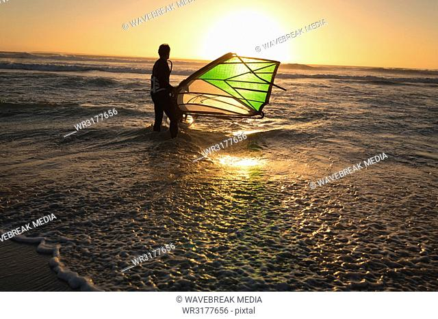 Male surfer surfing with surfboard and kite