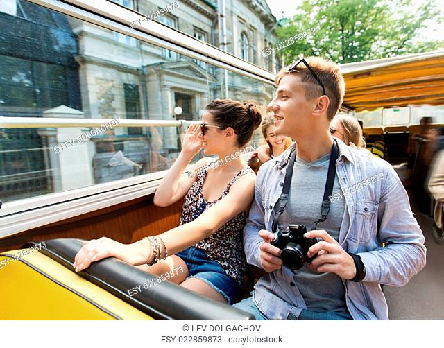 travel, tourism, summer vacation, sightseeing and people concept - smiling teenage couple with camera traveling by tour bus