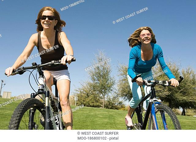 Two friends cycle side by side