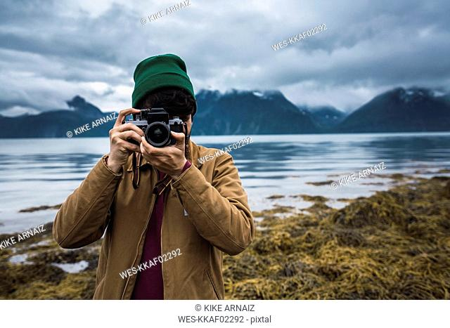 Young man with woolly hat taking pictures with camera