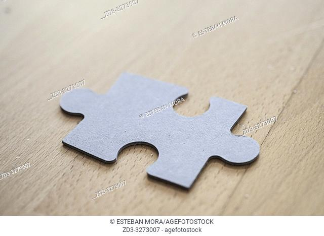 Puzzle piece on wood background
