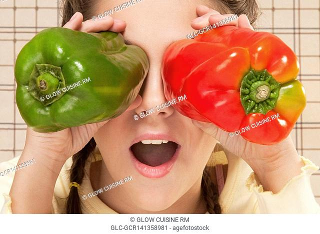 Close-up of a girl holding bell peppers over her eyes