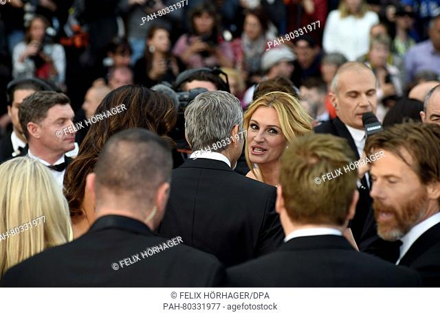 US actor George Clooney (m) and his wife Amal (l) and US actress Julia Roberts (r) arrive for the screening of 'Money Monster' during the 69th Annual Cannes...