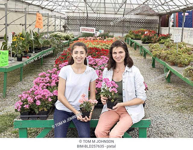 Smiling Caucasian mother and daughter holding flowers in nursery