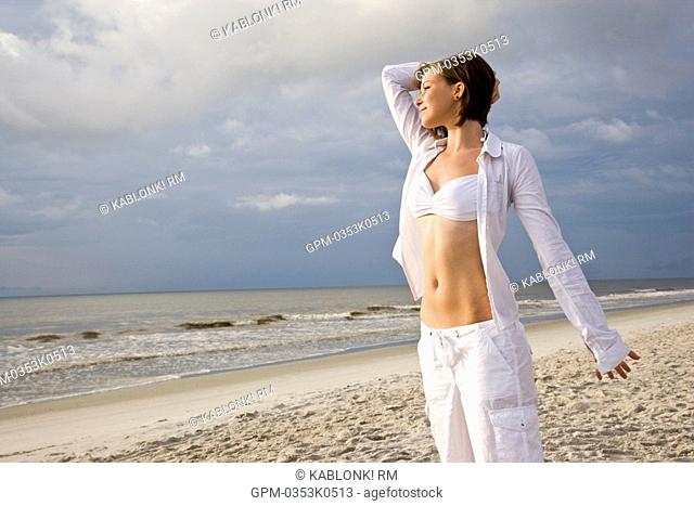 Young happy woman in white bikini top and pants standing on beach