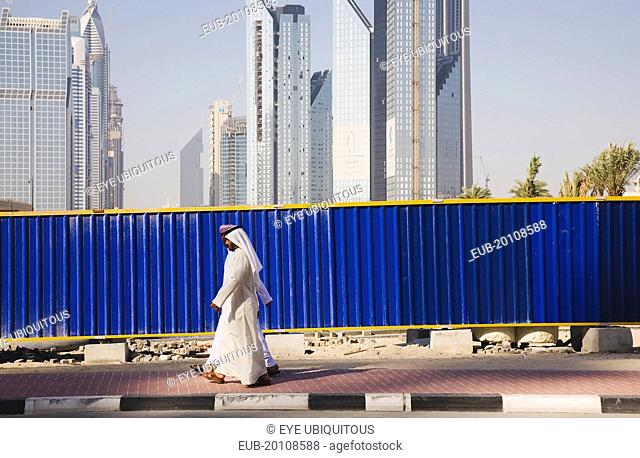 Arab men dressed in tradityional Dishdasha walking past construction site with Sheikh Zayed Road behind