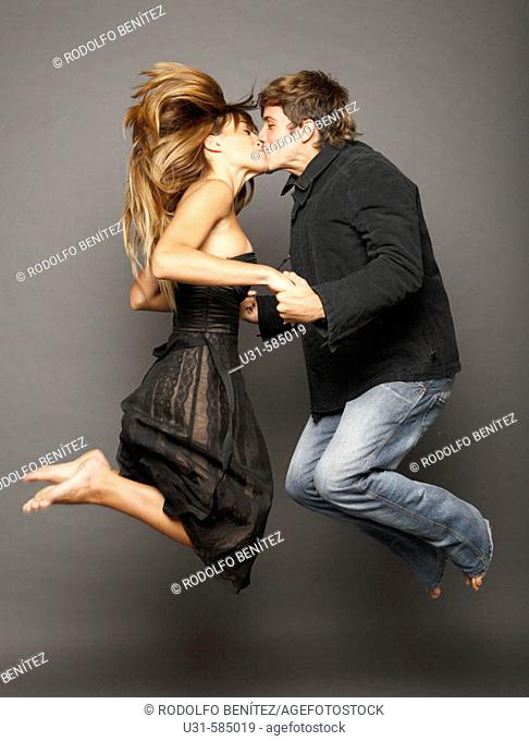 Young couple kissing in the air