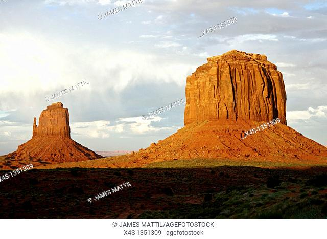 Massive sandstone pillars soar above iconic Monument Valley at sunset