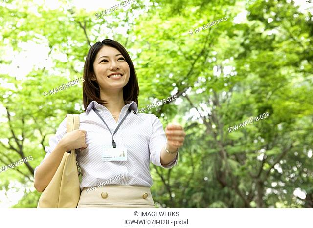 Japan, Osaka Prefecture, Businesswoman walking, smiling, low angle view